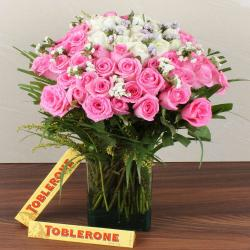 Mix Fresh Roses Glass Vase with Toblerone Chocolates for Dewas
