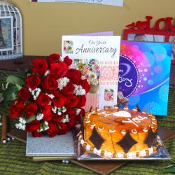 Red Roses Bouquet with Celebration Chocolates and Butterscotch cake Anniversary Greeting Card for Belgaum